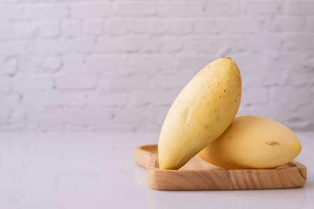 ripe yellow mangoes on white board. Stock fotó