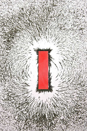 Bar magnet with iron filings showing magnetic field pattern