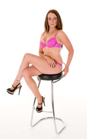 Woman in pink lingerie sitting on bar stool Stock Photo