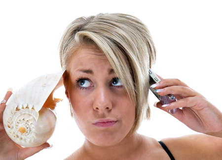 Young woman listening to conch shell and phone