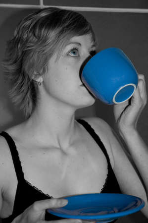 Woman in monochrome drinking from blue cup