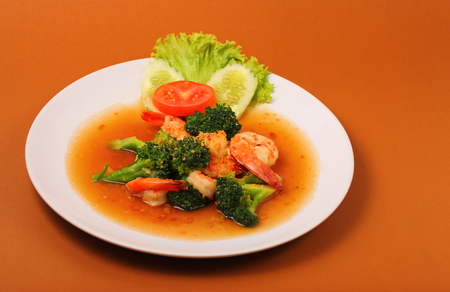 brocoli: Shrimp and broccoli stir fry in sauce with a brown background