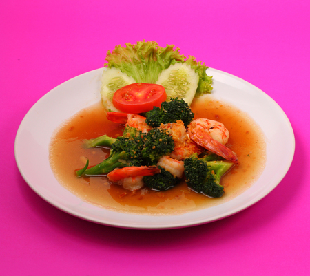 broccolli: Shrimp and broccoli stir fry in sauce with a pink background
