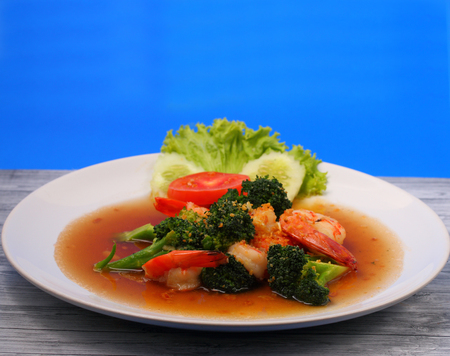 broccolli: Shrimp and broccoli stir fry in sauce with a blue background on a wood table Stock Photo