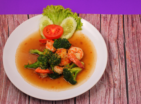 broccolli: Shrimp and broccoli stir fry in sauce with a purple background on a wood table