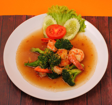 broccolli: Shrimp and broccoli stir fry in sauce with an orange background on a wood table