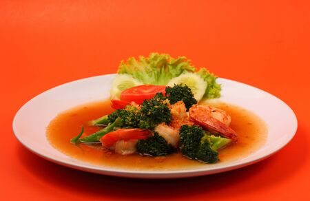 brocoli: Shrimp and broccoli stir fry in sauce with an orange background Stock Photo