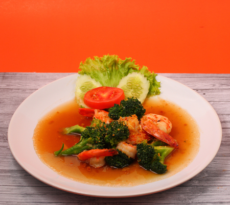 brocoli: Shrimp and broccoli stir fry in sauce with an orange background on a wood table
