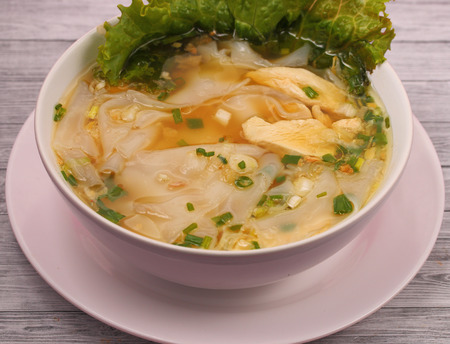 Glass noodle soup with chicken and beansprouts on a wood table top background photo