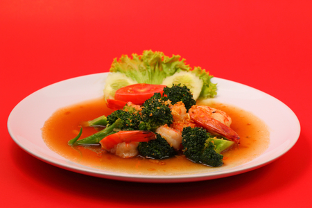 broccolli: Shrimp and broccoli stir fry in sauce with a red background Stock Photo