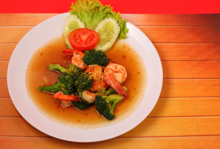 broccolli: Shrimp and broccoli stir fry in sauce with a red background on a wood table