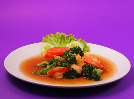 broccolli: Shrimp and broccoli stir fry in sauce with a purple background