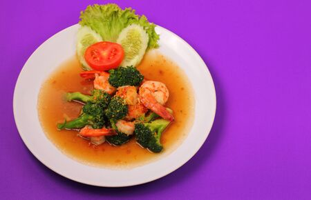 brocoli: Shrimp and broccoli stir fry in sauce with a purple background