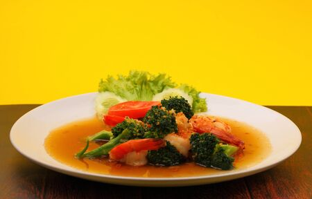 brocoli: Shrimp and broccoli stir fry in sauce with a yellow background on a wood table Stock Photo