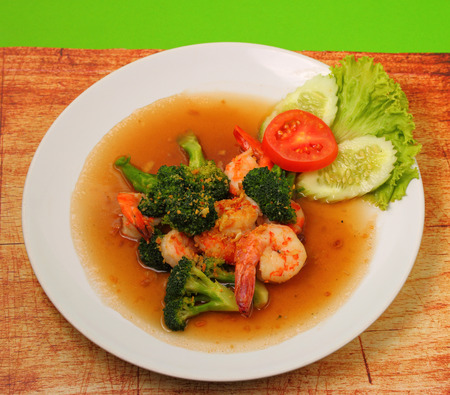 broccolli: Shrimp and broccoli stir fry in sauce with a green background on a wood table