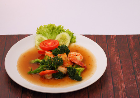 broccolli: Shrimp and broccoli stir fry in sauce with a white background on a wood table