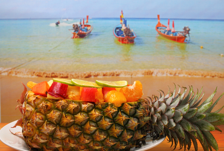 Thai style fruit salad inside a pineapple with a beach background on a wood table top photo