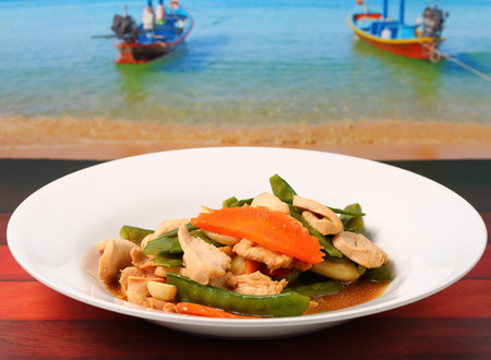chicken stir fry thai style on a wood table beside the beach photo