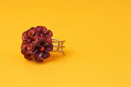 shiney: Flower decorated ring being displayed on a yellow background Stock Photo