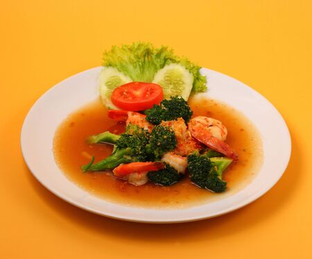 broccolli: Shrimp and broccoli stir fry in sauce with an orange background Stock Photo