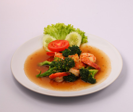 broccolli: Shrimp and broccoli stir fry in sauce with a white background