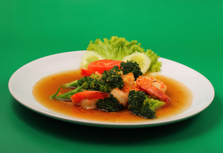 brocoli: Shrimp and broccoli stir fry in sauce with a green background