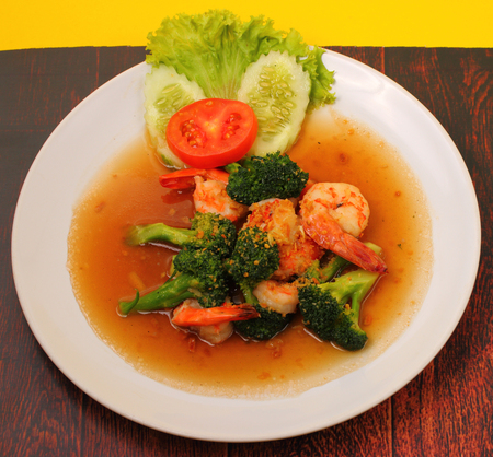 broccolli: Shrimp and broccoli stir fry in sauce with a yellow background on a wood table Stock Photo