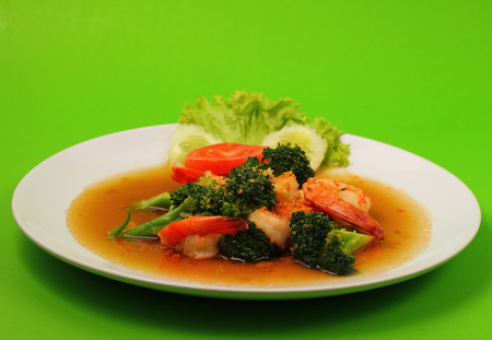 broccolli: Shrimp and broccoli stir fry in sauce with a green background