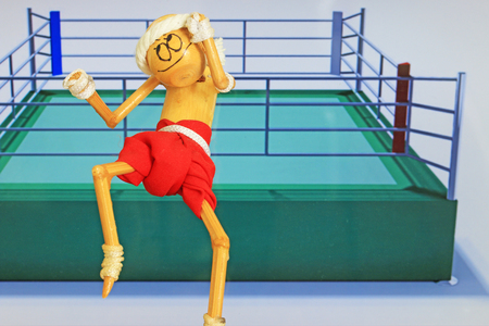 poised: Thai style boxing figure poised to box with boxing ring in background