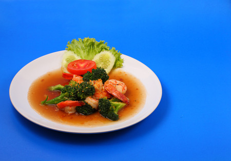 broccolli: Shrimp and broccoli stir fry in sauce with a blue background