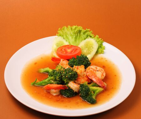 broccolli: Shrimp and broccoli stir fry in sauce with a brown background