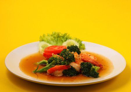 broccolli: Shrimp and broccoli stir fry in sauce with a yellow background