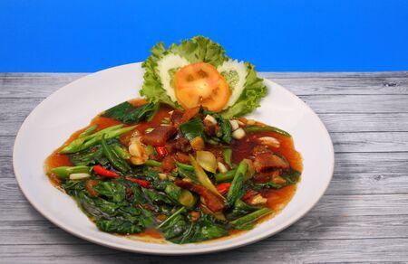 Thai style Crispy pork stir fry with a blue background on a wood table top photo