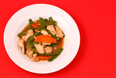 chicken stir fry thai style on a red background photo