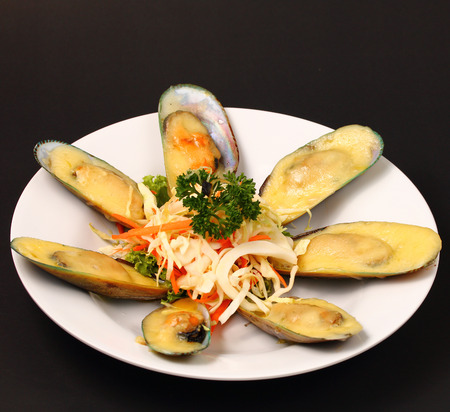 phuket food: new Zealand mussels in cheese sauce with a black background