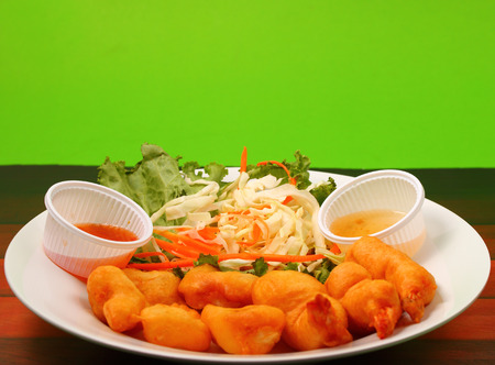 seafood salad: thai style seafood salad with a green background on a wood table top