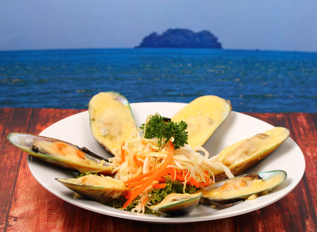 phuket food: new Zealand mussels in cheese sauce on a wood table top on the beach Stock Photo