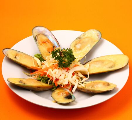 phuket food: new Zealand mussels in cheese sauce with an orange background