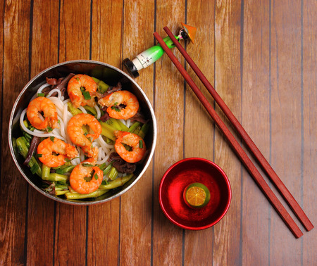 rice noodles: Vietnamese shrimp and rice noodles soup pho, served on a wood table top
