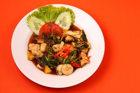 stir fry: thai style seafood stir fry with an orange  background Stock Photo