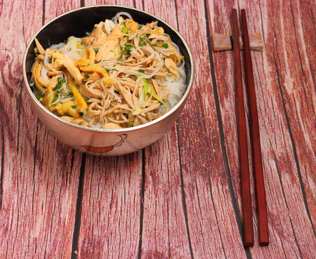 rice noodles: Vietnamese vermicelli chicken and rice noodles soup, pho, on a wood table top