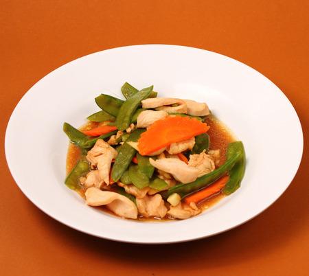 chicken stir fry thai style on a brown background photo