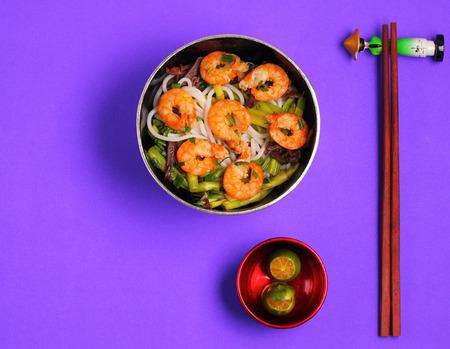 rice noodles: Vietnamese shrimp and rice noodles soup, pho, with a purple background