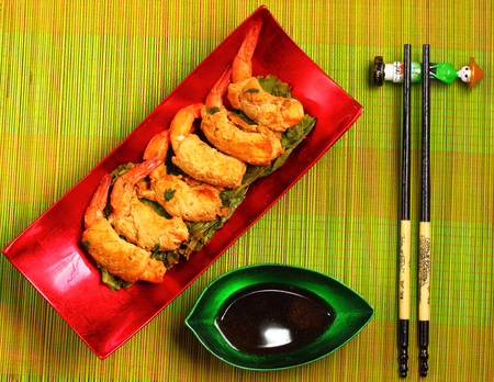 breadcrumbs: traditional Vietnam deep fried shrimp and pork rolls in breadcrumbs served on a traditional bamboo place mat Stock Photo