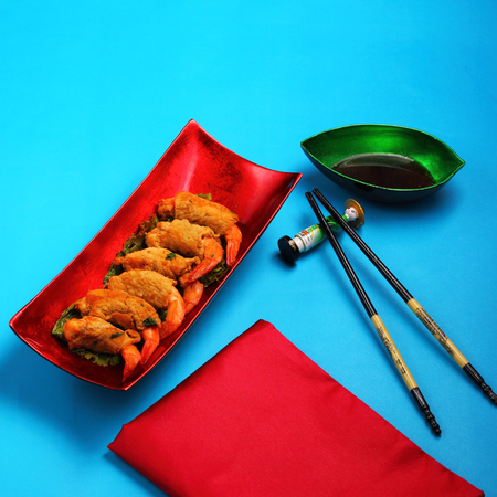 breadcrumbs: traditional Vietnam deep fried shrimp and pork rolls in breadcrumbs served on a blue background