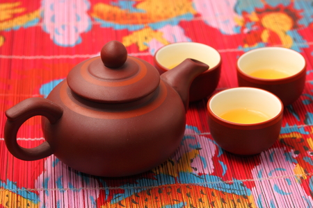 spout: Asian tea set served on a bamboo place mat Stock Photo