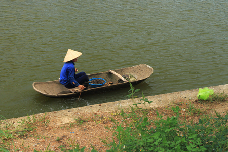conical hat: vietnam woman fishing on boat Editorial