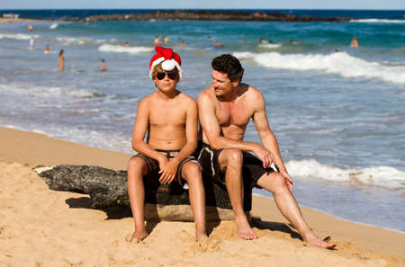 Teen Boy and his Father sitting on a log at the Beach in Hawaii and the Teenager is wearing a Santa Hat photo