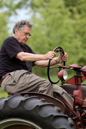 rugged: Retired Farmer Driving a Vintage Tractor Stock Photo