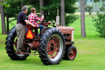 Grandfather teaching his Grandson how to drive a stick shift on a Old Vintage Tractor photo